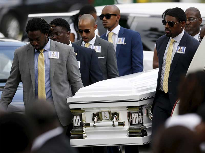 Individual lifting the casket